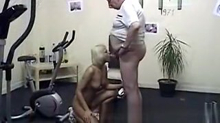 Young blond beauty thanks her filthy old trainer in the gym