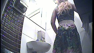 Gorgeous blonde white girl in sexy dress pisses in the toilet room