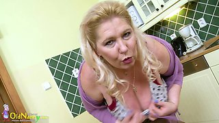 Mature blonde stripping and playing with her huge boobs in the kitchen