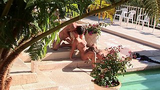 Busty friends helping their partner with her erection by the pool