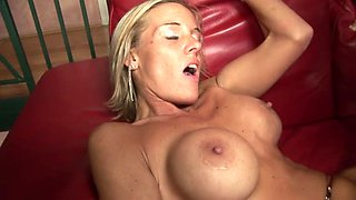 Blonde MILF plays with her big fake tits while riding cock hardcore