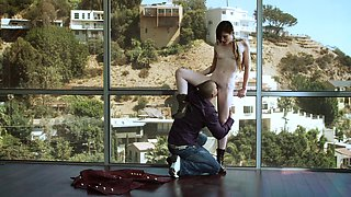Stoya is pressed up against a window and fucked from behind